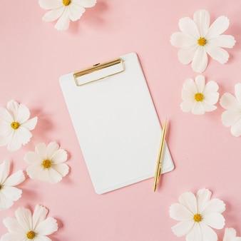 최소한의 스타일 개념. 흰색 정제와 금 펜 옅은 분홍색에 흰색 데이지 카모마일 꽃. 창의적인 라이프 스타일, 여름, 봄 개념