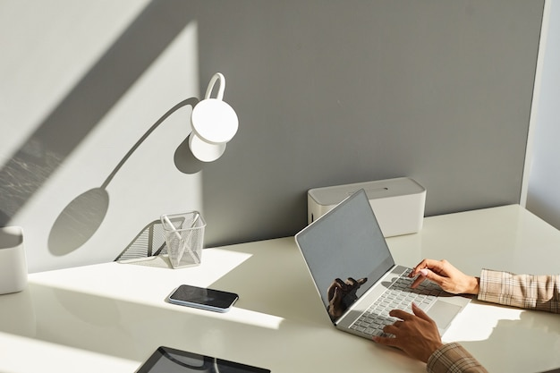 Minimal surface image of unrecognizable woman using laptop on white workplace desk with focus on elegant female hands typing on keyboard in sunlight, copy space