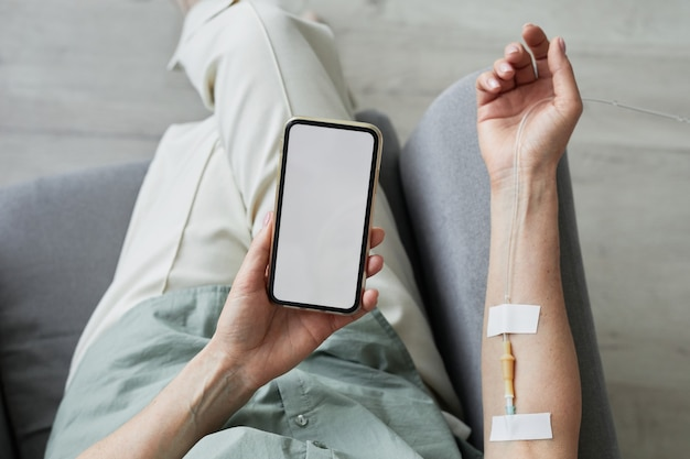Minimal top view close up of unrecognizable woman getting iv drip and using smartphone with blank screen, copy space