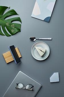 トロピカルリーフと灰色の職場の背景の上にチーズケーキとビジネスアクセサリーの最小限の上面図フラットレイ、