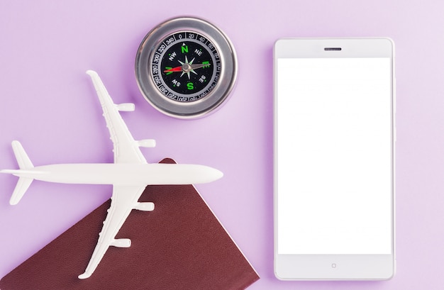 Minimal toy model plane, compass and modern smart mobile phone blank screen