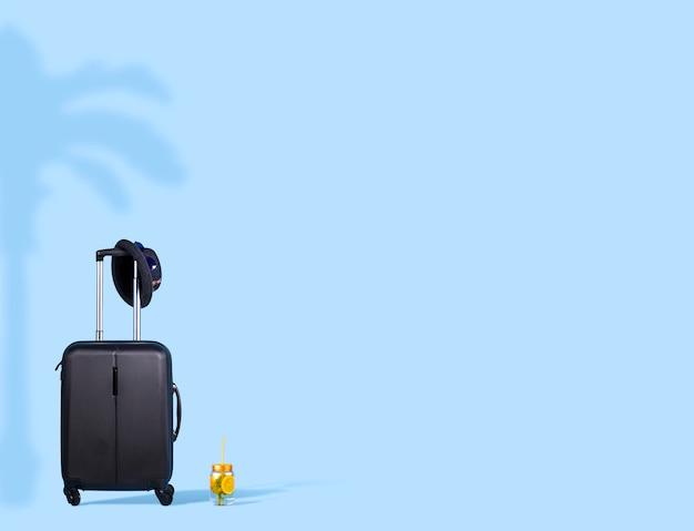 Минимальный туристический состав. черный чемодан со шляпой, солнцезащитными очками и свежим коктейлем
