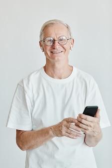 Минимальный вертикальный портрет улыбающегося старшего мужчины, держащего смартфон и смотрящего в камеру против белого ...