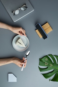 Minimal above view flat lay of woman eating cheesecake over grey workplace background with tropical leaf and business accessories,