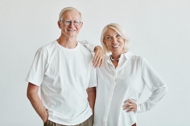 Minimal waist up portrait of modern senior couple wearing white against white background and smiling...