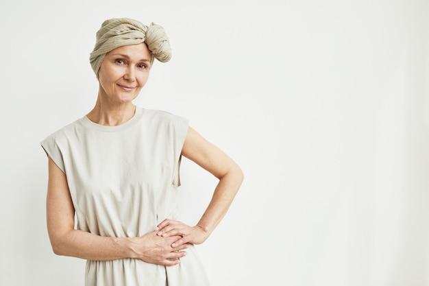 머리 스카프를 착용하고 카메라를 보며 웃고 있는 아름다운 성숙한 여성의 최소 허리 초상화, 복사 공간