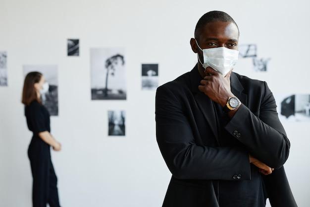 現代アートギャラリー、コピースペースで写真を見ながらマスクを身に着けているエレガントなアフリカ系アメリカ人の男性の最小限のウエストアップの肖像画