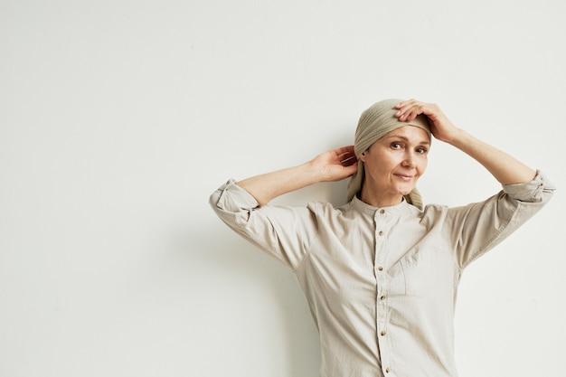 흰 벽 옆에 서 있는 동안 머리 스카프를 두르고 카메라를 바라보며 웃고 있는 성숙한 여성의 최소 허리 초상화, 복사 공간