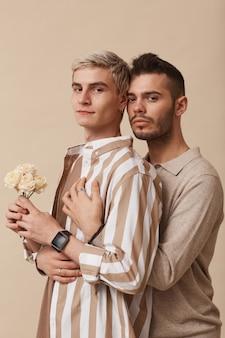 Минимальная талия портрет молодой гей-пары, обнимающей и держащей цветы, позируя на нейтральном бежевом фоне в студии