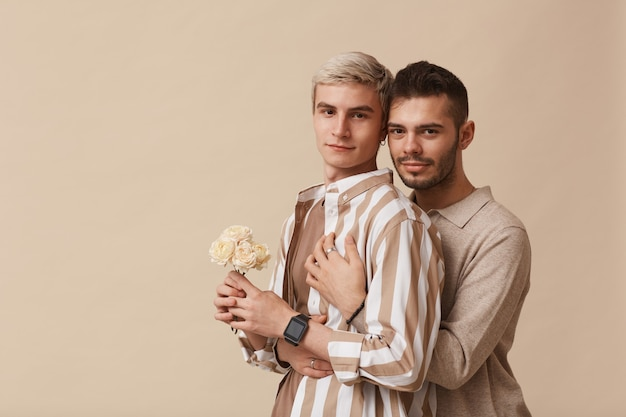 Минимальная талия портрет молодой гей-пары, обнимающей и смотрящей в камеру, позируя с цветами на нейтральном бежевом фоне в студии, копией пространства