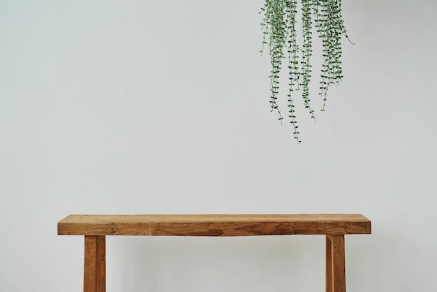 天使のつる植物と木製のベンチと最小限の壁