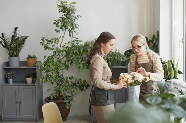 Минимальный широкоугольный портрет двух молодых женщин, собирающих букеты, наслаждаясь работой в студии флористов, копировальное пространство