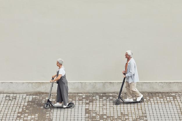 Минимально широкий угол обзора современной зрелой пары, катающейся на электрических скутерах в серой городской среде, копировальное пространство