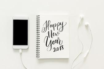 最小限の作業スペース - スケッチブックの「2018年新年あけましておめでとうご」とワークスペースデスクの創造的な平らな写真。白い背景に空白の画面とイヤホンが付いている携帯電話。トップビュー、新年のコンセプト。