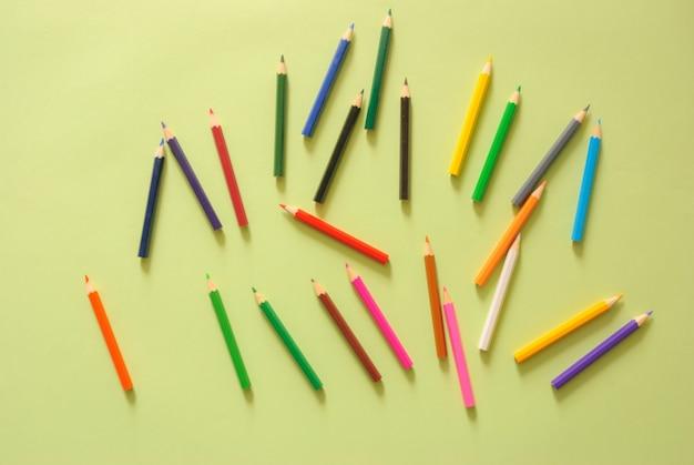 最小限の作業スペース - コピースペースにカラー鉛筆でワークスペースデスクのクリエイティブフラットレイ写真グリーンパステルの背景。トップビュー、フラットレイ写真。