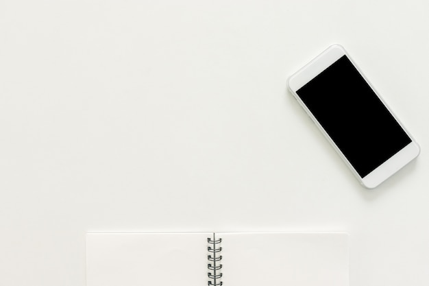最小限の作業スペース - スケッチブックとコピースペースの空白の画面と携帯電話のワークスペースデスクのクリエイティブフラットレイ写真白い背景。トップビュー、フラットレイ写真。