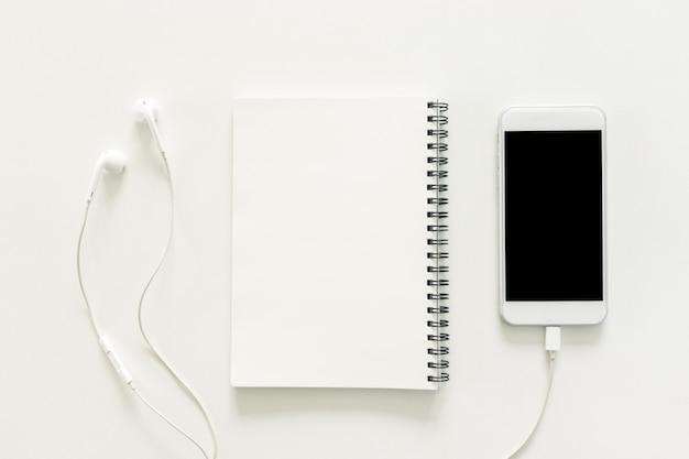 最小限の作業スペース - スケッチブックとコピースペースの白い背景に空白の画面と携帯電話のワークスペースデスクのクリエイティブフラットレイ写真。トップビュー、フラットレイ写真。