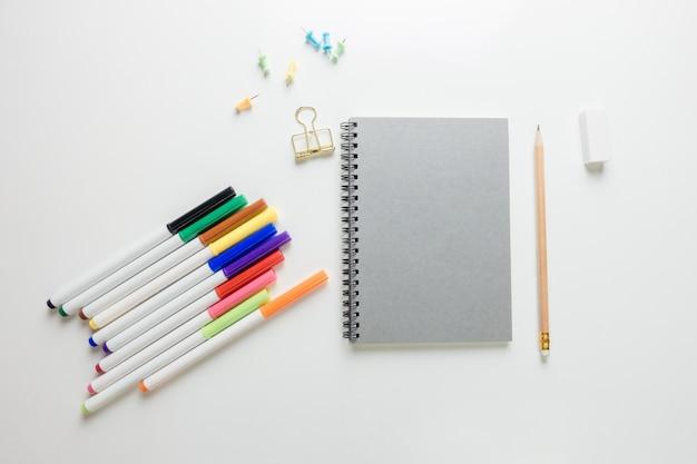 最小限の作業スペース - スケッチブックとコピースペースの上に木製の鉛筆とワークスペースデスクのクリエイティブフラットレイ写真白い背景。トップビュー、フラットレイ写真。