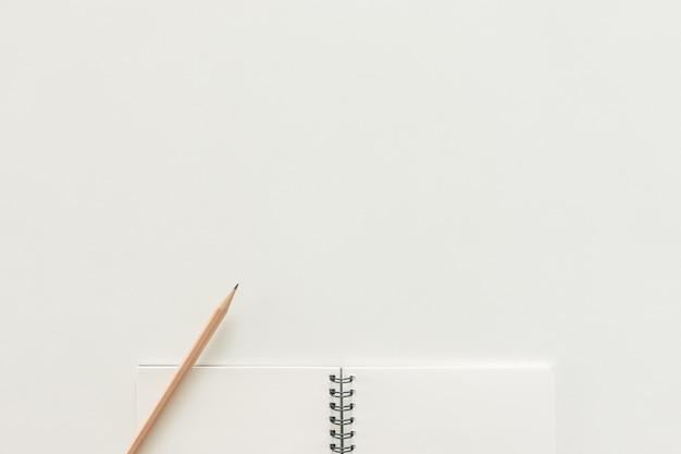 Минимальное рабочее пространство - творческая квартира лежал фото рабочего стола стола с альбомной книги и деревянный карандаш на фоне копирования пространства на белом фоне. вид сверху, плоская фотография.