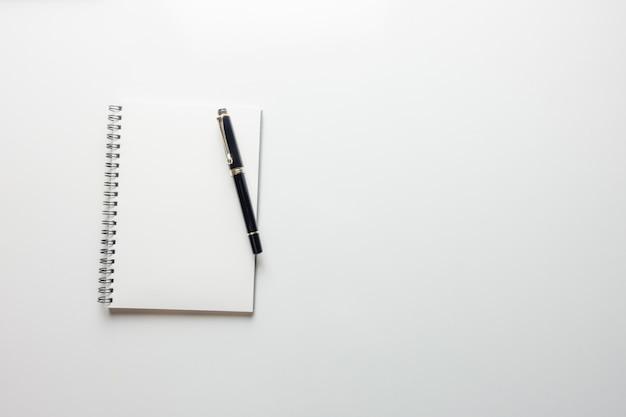 最小限の作業スペース - スケッチブックとコピースペースの木製鉛筆でワークスペースデスクのクリエイティブフラットレイ写真白い背景。トップビュー、フラットレイ写真。