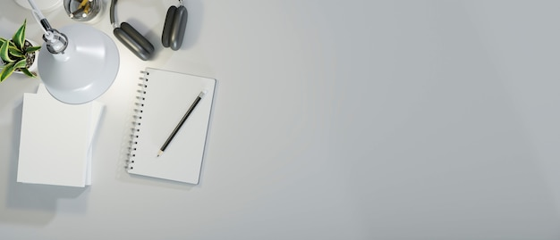 本のヘッドフォンとテーブルランプの上面図からの光で白い装飾の最小限の作業スペース
