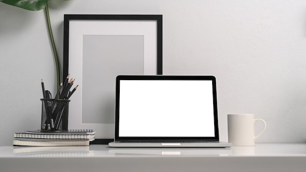 コンピューターのラップトップ、鉛筆ホルダー、黒い空のフォトフレームと白いテーブルの上のコーヒーカップと最小限の職場