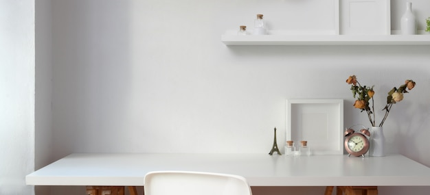 Minimal workplace with copy space and decorations on white table with white wall