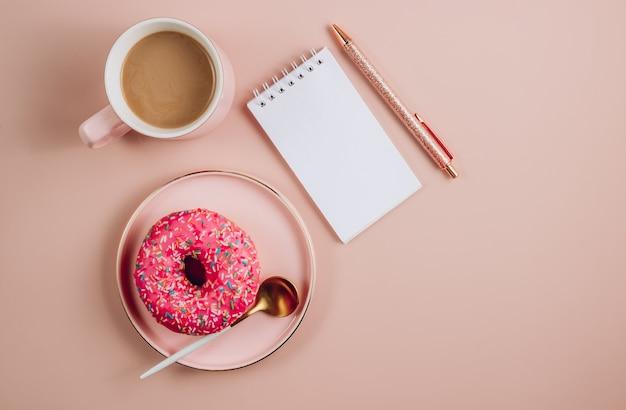 白い空白のノートブック、コーヒーカップ、ピンクの背景にドーナツと最小限の職場