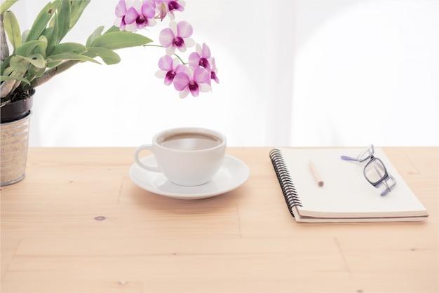 최소한의 작업 공간, 커피 컵, 난초 꽃, 안경 및 나무 테이블에 노트북