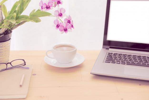 최소한의 작업 공간, 컴퓨터 노트북, 커피 컵, 난초 꽃과 나무 테이블에 노트북
