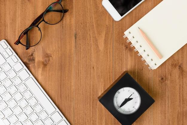 最小限のワークスペース、コンピューター、スマートフォン、ノートブック、鉛筆、木製のテーブル、上面図