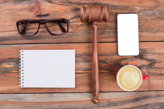 Minimal workspace mobile phone gavel cup of coffee on wood table
