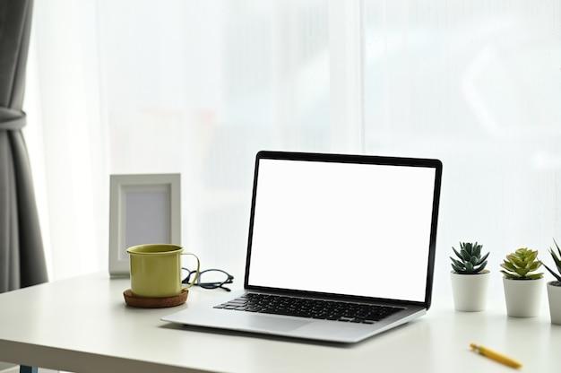最小限のワークスペースは、白いテーブルに空の画面のコンピューターのラップトップ、サボテン、コーヒーカップをモックアップします。