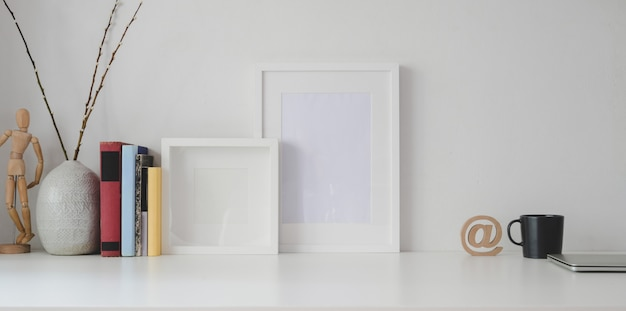 Minimal workspace with blank frame and office supplies on white wooden table