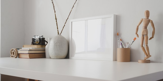 Minimal workspace with blank photo frame and office supplies on white wooden table and white wall