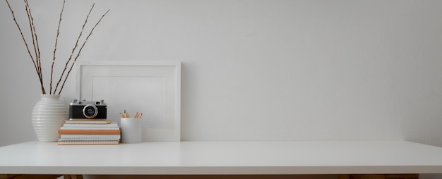 Minimal workspace with camera, books, decorations and copy space