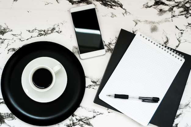 Minimal workspace with coffee cup, notebook, smartphone on stylish marble
