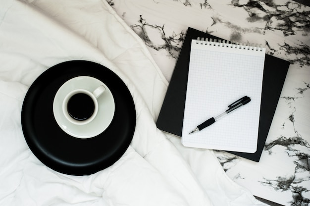 Minimal workspace with coffee cup, notebook with copy space on stylish marble background