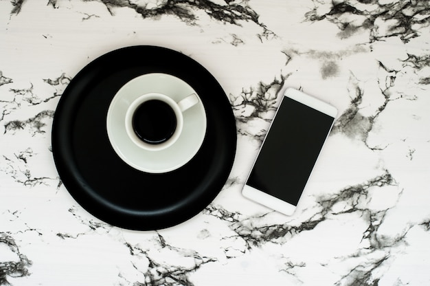Minimal workspace with coffee cup, smartphone on stylish marble