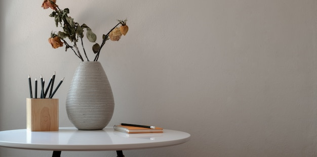 Minimal workspace with dry roses vase and office supplies on white table