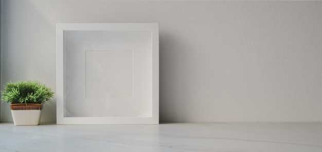 Minimal workspace with mock up frame and tree pot on white wooden table and white wall background