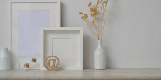 Minimal workspace with mock up frames and decorations in white wall background
