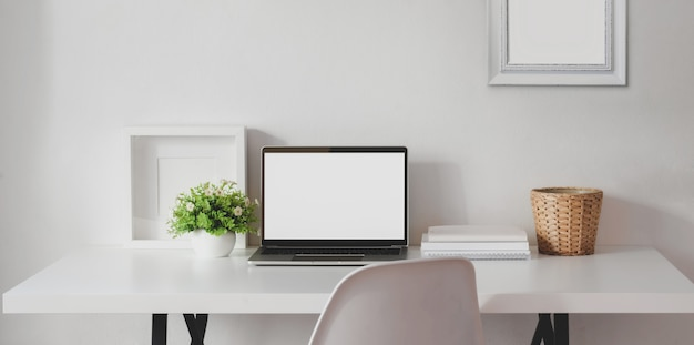 Minimal workspace with open blank screen laptop computer with mock up frame