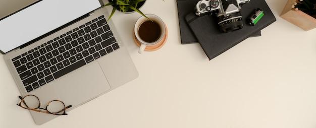 복사 공간, 실물 크기의 노트북, 안경, 커피 컵, 카메라, 문구 및 장식이있는 최소 작업대