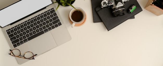 Minimal worktable with copy space, mock-up laptop, glasses, coffee cup, camera, stationery and decoration