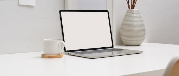 モックアップラップトップ、本、コーヒーカップ、装飾を備えた最小限の作業台