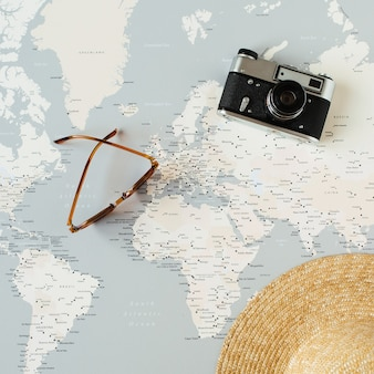 Minimal world map with pins, retro camera, sunglasses, straw hat. flat lay vacation travel planning