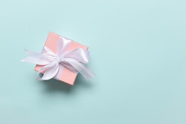 미니멀리즘. 흰색 활이 있는 분홍색 상자에는 텍스트를 위한 자리가 있습니다. 평면 레이아웃, 평면도, 복사할 장소.