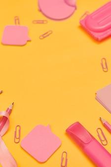 노란색 배경 플랫 레이 복사 공간에 학교 개념으로 돌아가는 미니멀리즘 분홍색 학교 용품