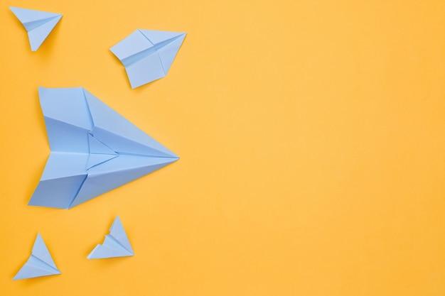 노란색 배경에 미니멀리즘 파란색 종이 비행기